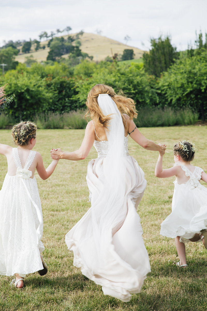 Bride and flower girls skipping away